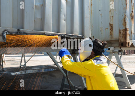 Industry worker with protective mask welding steel to repair container structures manufacture workshop. Worker welding - Stock Photo