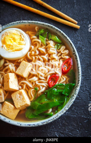 Japanese ramen soup with tofu and egg on dark stone background. Miso soup with ramen noodles and tofu in ceramic - Stock Photo