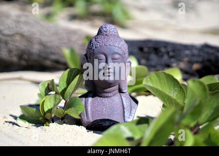 Selective focus meditating Buddha statue on sand in outdoor setting - Stock Photo