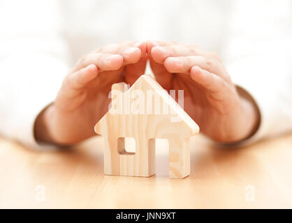 Wooden toy house protected by hands - Stock Photo