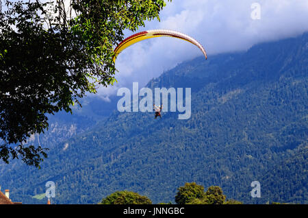 Paragliding in Alps (Switzerland) in Interlaken, Jungfrau Region; Slopes of Mountains covered with Forests in the - Stock Photo
