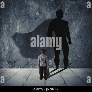 Young businessman with his shadow of super hero on the wall. Concept of powerful small man - Stock Photo