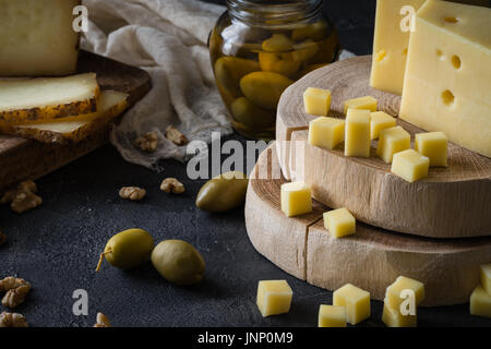 Cheese platter of chopped Swedish hard cheese and sliced and Italian pecorino toscano) on wooden boards, with green - Stock Photo