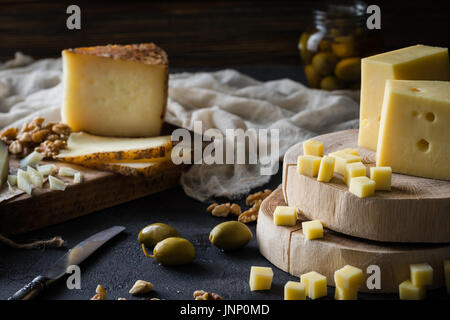 Cheese platter of chopped Swedish hard cheese and sliced Spanish manchego and Italian pecorino toscano) on wooden - Stock Photo