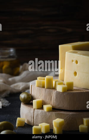 Swedish hard yellow cheese with holes chopped on wooden slices with green olives on dark rustic background - Stock Photo