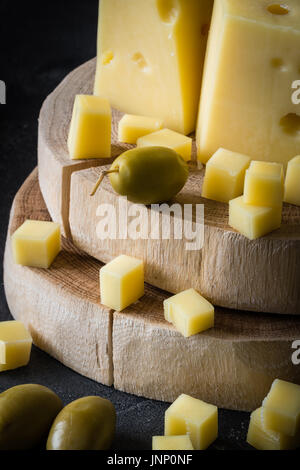 Close up of Swedish hard yellow cheese with holes chopped on wooden slices with green olives on dark rustic background - Stock Photo