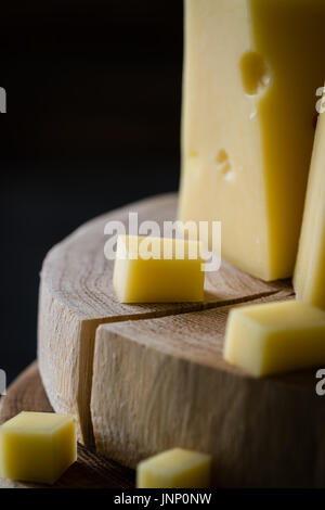 Close up of Swedish hard yellow cheese with holes chopped on wooden slices on dark rustic background - Stock Photo