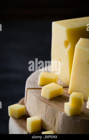 Closeup of Swedish hard yellow cheese with holes chopped on wooden slices on dark rustic background - Stock Photo