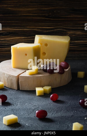 Swedish hard yellow cheese with holes chopped with red grapes on wooden slices on dark rustic background - Stock Photo