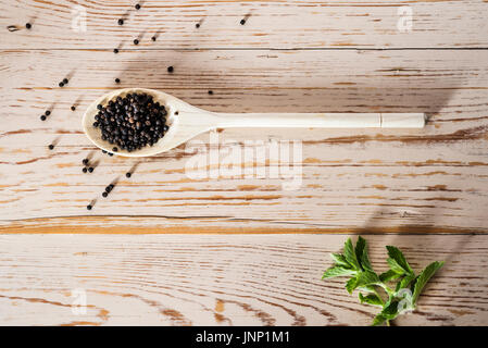 Overhead shot of wooden spoon on distressed table top, with black peppercorns. - Stock Photo