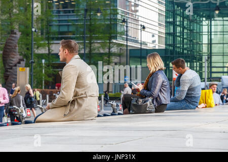 London, UK - May 10, 2017 - People sitting on a low wall outside Canary Wharf tube station - Stock Photo