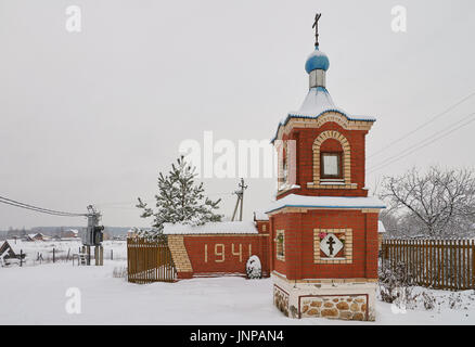 Winter view of red brick chapel and monument to soviet warriors who died in Second World War. Ignatovo village, - Stock Photo