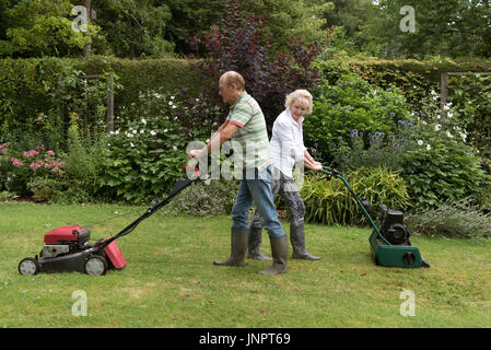 Man and woman with lawn mowers working in a country garden - Stock Photo