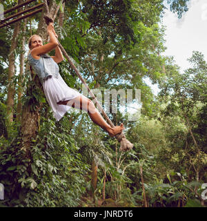 Family travel lifestyle. Happy young woman flying high with fun on rope swing on wild jungle background. Funny adventure - Stock Photo