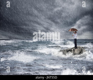 Businessman with umbrella during storm in the sea. Concept of insurance protection - Stock Photo