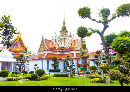 The monastic quarters complex with giant demon figures and topiary trees at Wat Arun (Temple of Dawn) in Bangkok, - Stock Photo