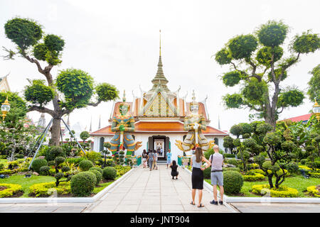 The entrance (Phra Ubosot) to monastic quarters complex with giant demon figures and topiary trees at Wat Arun (Temple - Stock Photo