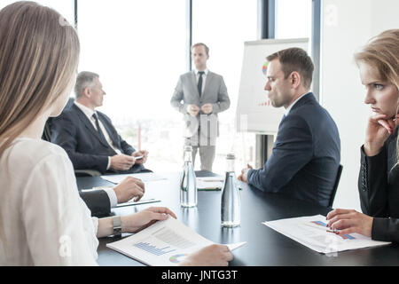 Group of business people at meeting watching presentation of reports in diagrams and graphs at flip chart in offfice - Stock Photo