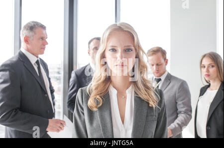 Portrait of a young woman in front of business people team