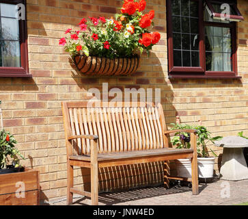 English back Garden with wooden bench seat and flower filled basket of Begonias on the wall - Stock Photo