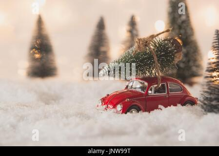 Little red car toy carrying Christmas tree in snow covered miniature forest - Stock Photo
