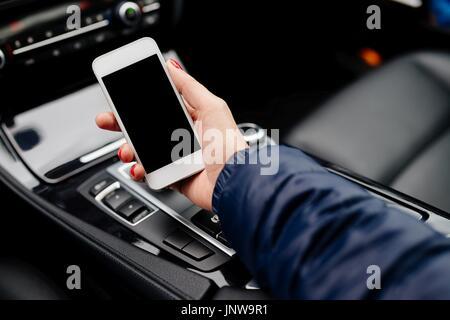 Woman using white smartphone in car. Modern car interior - Stock Photo