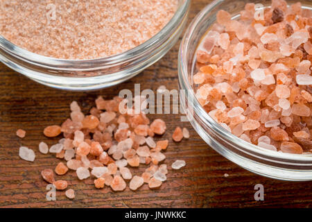 fine and coarse crystals of pink  Himalayan salt in glass bowls on rustic wood - Stock Photo