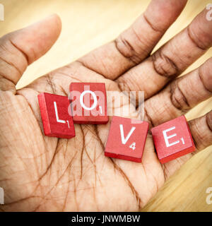 White letters on reddish wooden blocks from a work game spell the word 'love' in the palm of a person's hand. Their - Stock Photo