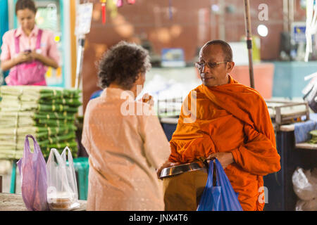 Bangkok, Thailand - February 18, 2015: Monk receiving alms at Pak Khlong Talat market in Yaowarat and Pahurat in - Stock Photo