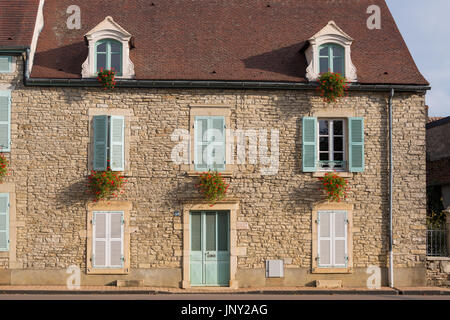 Beaune, Burgundy, France - October 11, 2015: Stone house with pale green shutters and red geraniums in window boxes, - Stock Photo