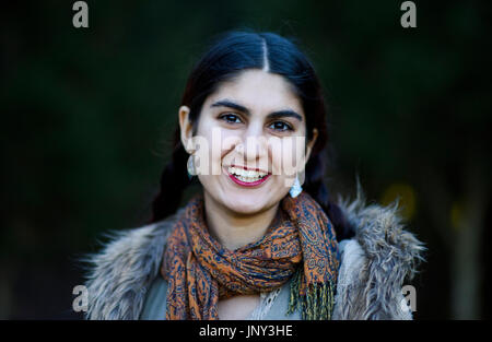 Teenage Persian girl walking in the park on an autumn day - Stock Photo