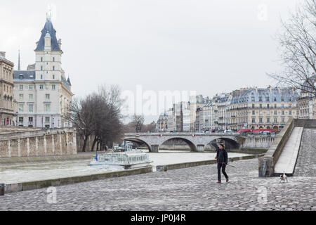 Paris, France - March 2, 2016: Young woman walking her dog by the Seine across from Ile de la Cite and Pont Saint - Stock Photo