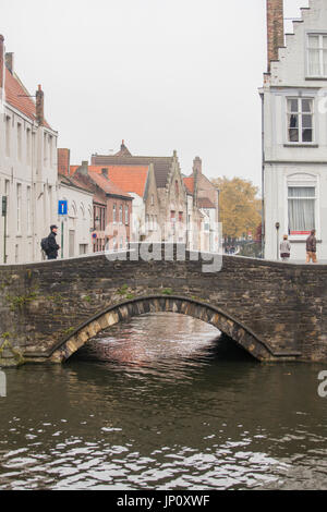 Bruges, Belgium – October 31, 2010: Pedestrians and bridge over canal in Bruges. - Stock Photo