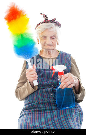 Portrait of a happy senior lady doing housework holding cleaning equipment - Stock Photo