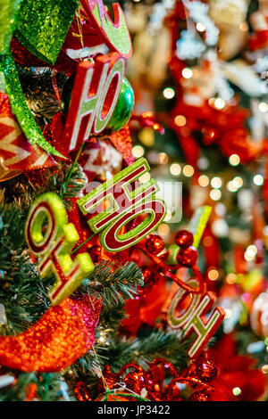 Christmas tree decorations and lights hanging on a traditional Christmas tree during the Christmas holiday season. - Stock Photo