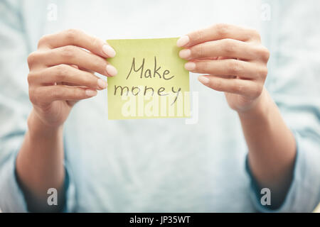 Woman holding sticky note with Make money text - Stock Photo