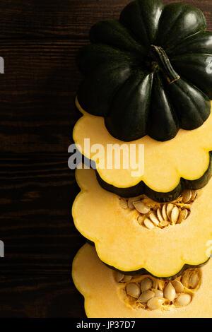 Sliced raw acorn squash on dark background - Stock Photo