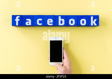 facebook logo made from blue cubes and human hand holding smartphone on yellow surface - Stock Photo