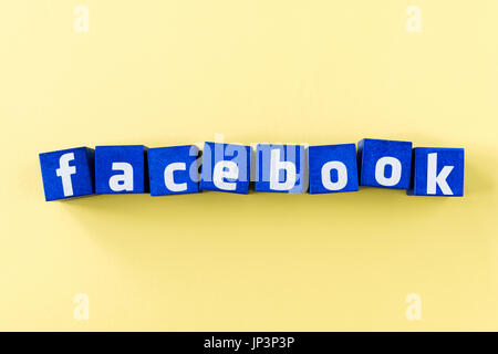 facebook logo made from blue cubes with smartphone on yellow surface
