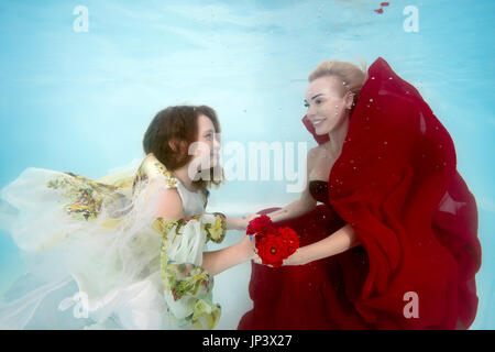 Woman in red dress with teen daughter posing under water in the pool - Stock Photo