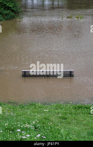 river flood with flooded park bench - Stock Photo