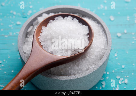 sea salt in stone bowl and wooden spoon - Stock Photo