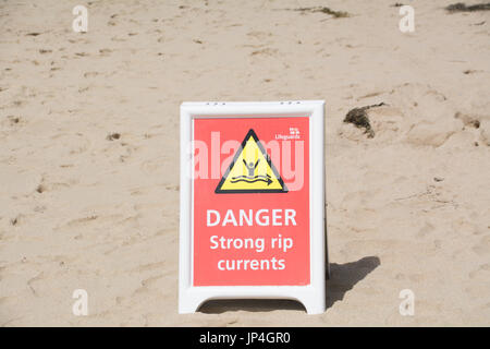 Danger strong rip currents sign on beach - Stock Photo