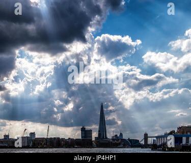 London,Uk.London skyline with sun shining through black cloudy sky. Rays of light, the Shard,dark clouds. - Stock Photo
