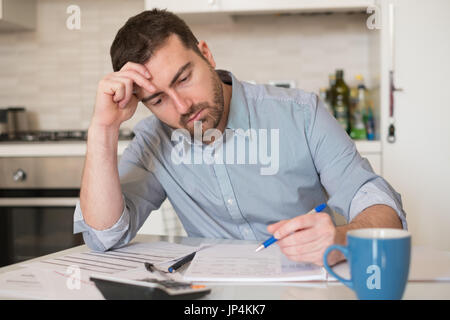 Frustrated man calculating bills and tax  expenses - Stock Photo