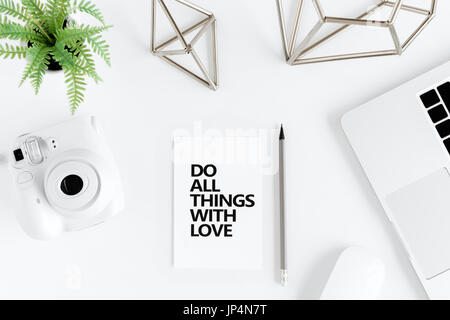 Top view of do all things with love motivational quote and instant camera at workplace - Stock Photo