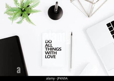 flat lay with Do all things with love motivational quote on modern workplace with wireless devices - Stock Photo