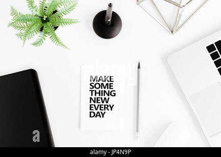 flat lay with Make something new everyday motivational quote on modern workplace with wireless devices - Stock Photo