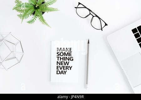 Top view of make something new everyday motivational quote and laptop at workplace - Stock Photo