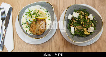 Fish cakes served with a fried egg plus samphire and courgette salad with feta cheese at the Square Chapel Arts - Stock Photo